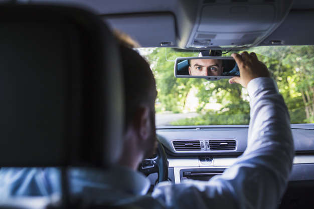 a father adjusting the rearview mirror so that his child's seat is visible to him at all times.