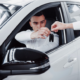 two-men-stand-showroom-against-cars-close-up-sales-manager-suit-that-sells-car-customer-seller-gives-key-customer
