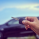 a person holding a car key with a blurred background of a car