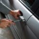 A person trying to open a car using a screwdriver